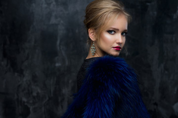 Close-up portrait of gorgeous blonde young woman in celebrity style with perfect make up and hair style wearing blue fur. Fashion beauty photo, dramatic look