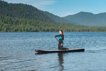 Smiling woman paddle boarding on knees at the mountain lake
