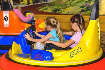 Mädchen haben Spaß beim Scooterfahren im Freizeitpark