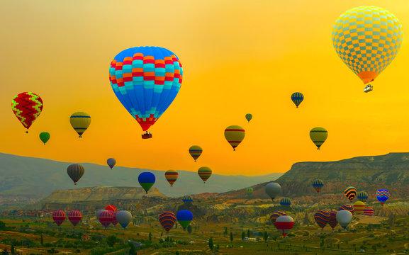 Hot air balloon over yellow landing in a mountain