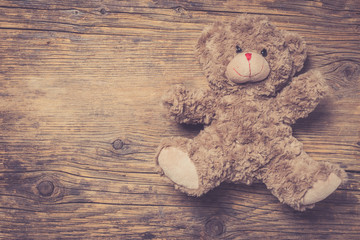 Brown teddy bear over wooden background