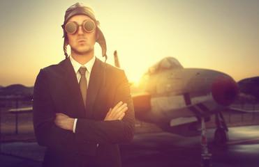 Geschäftsmann mit Pilotenkappe vor altem Flugzeug