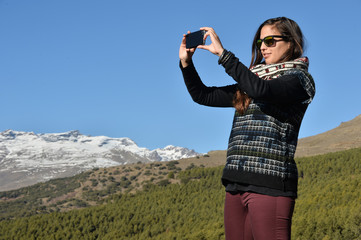 Young girl taking pictures of the mountain