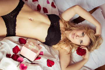 pink gift box and enjoying in pleasure, looking at camera elegant green eyes pretty lady romantic pinup silk skin female having fun smiling relaxing laying on light copy space background