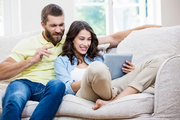 Couple sitting on sofa and using digital tablet in living room