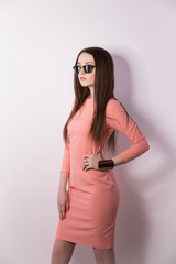 Portrait of young brunette posing against white wall in stylish sunglasses and pink dress.