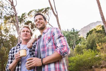Male friends drinking tea in wilderness