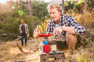 Mature man frying on camping stove in forest, Deer Park, Cape Town, South Africa