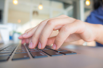 Closeup of business woman hand typing on laptop keyboard with mo