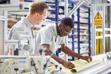 Two men working in factory