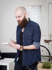 Young hipster man taking notes with pen at home during day.