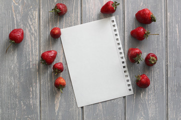 Strawberries on wooden grey desk with white paper sheet.