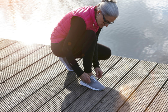 Woman wearing pink bodywarmer and earbuds crouching on pier tying shoelace