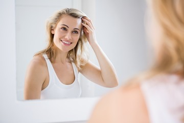 Young woman checking her hair in bathroom mirror