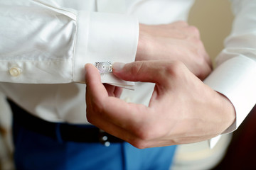 Groom is wearing cufflinks indoors. Male portrait of handsome guy. Beautiful model boy in colorful wedding clothes. Man is posing