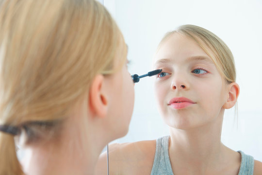 Over the shoulder mirror image of girl applying mascara