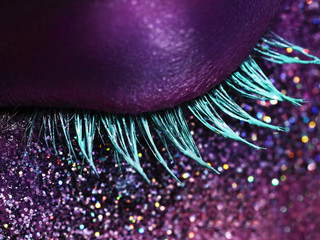 Close up of a woman's closed eye with iridescent make up