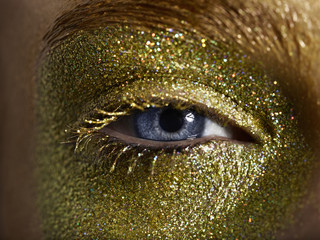 Close up of a woman with gold eye make up