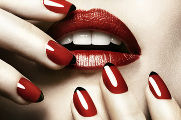 Detail of woman's mouth and hands wearing red lipstick and nail varnish