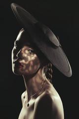 Portrait of woman wearing a black hat in shadow