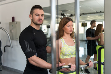 Woman Train Biceps On Machine With Personal Trainer