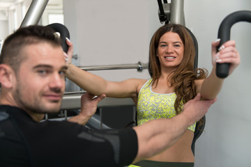 Woman Train Chest On Machine With Personal Trainer