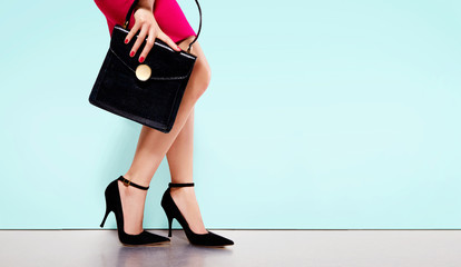 Woman with red skirt holding beautiful leather black hand bag wearing high heels. isolated on light blue background.copy space.