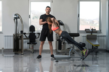 Gym Coach Helping Woman On Back Exercise