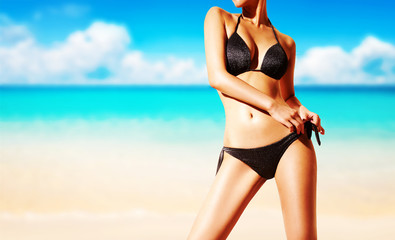 Beautiful body woman with black bikini swim suite on the beach. Copy space.