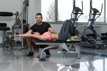 Gym Coach Helping Woman On Chest Exercise