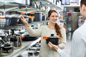 Smiling positive  couple in the cookware section