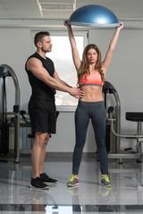 Personal Trainer Helping Woman On Bosu Push Ups