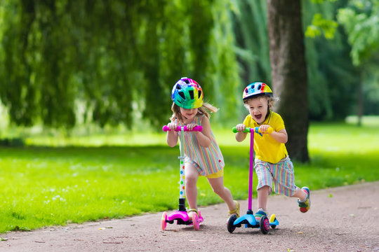 Little kids riding colorful scooters