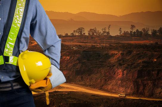 Engineer holding yellow helmet with coal mining