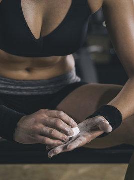 Female athlete coating his hands in powder chalk magnesium