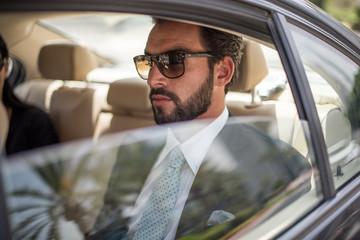 Young businessman wearing sunglasses in car backseat, Dubai, United Arab Emirates