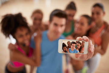 Mobile phone as photo camera in gym, selfie concept