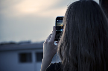 Girl taking photo of the sunset