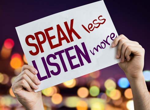 Speak Less Listen More placard with night lights on background