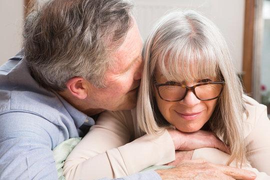 Man whispering into wife's ear