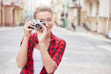 Beautiful young woman makes a photo on a city street.