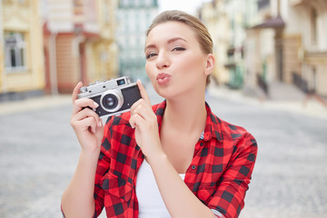 Beautiful young woman holding a camera and sending kiss to the camera.