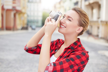 Beautiful young woman makes the photo in the city. Tourism
