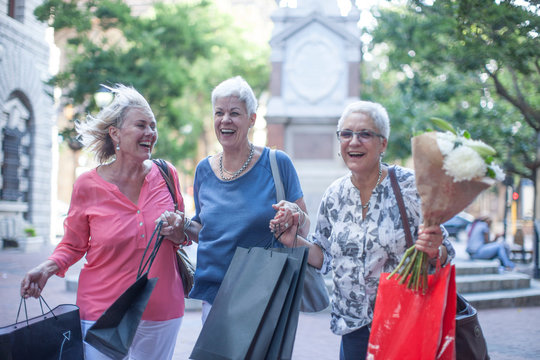 Happy senior and mature women carrying shopping and bouquet in city