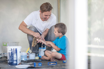 Builder helping son to clean up