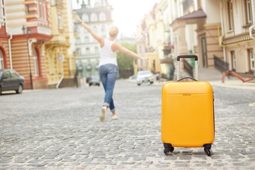 Orange suitcase on the road in city and young woman on the background. Summer vacation and travel concept