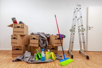 Sauberer, weißer Raum mit Kartons und Putzzeug