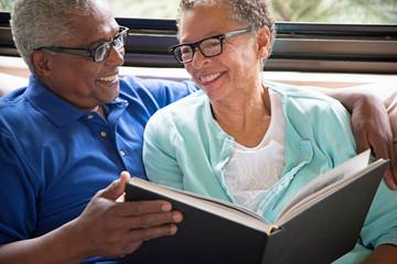 Senior couple sitting on sofa, looking through photo album