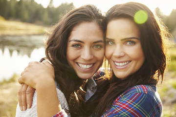 Lesbian couple hugging by a lake look to camera, close up
