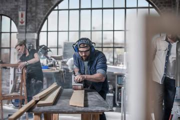 Man using sander in workshop
